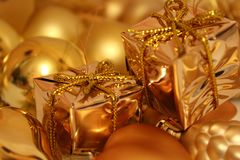 Christmas toys of different shapes of gold color, bright background. royalty free stock photography