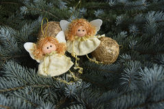 Christmas toys in the form of angels and a gold sphere Stock Images