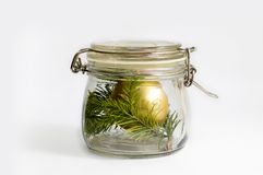 Gold Christmas ball and spruce branch in a glass jar. Isolated on white stock photography
