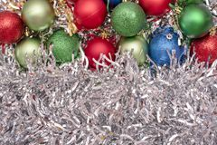 Christmas toys of green, blue and red colors on the background of silver tinsel. Beautiful Christmas toys of green, blue and red colors on the background of stock photography