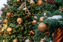 Christmas toys on the green tree with snow. Golden ball close-up, Christmas toys and shiny balls. Christmas in the street. Photo shot bokeh stock images