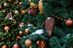 Christmas toys on the green tree with snow. Spruce cone closeup, golden shiny balls. bokeh. Christmas toys on the green tree with snow. Spruce cone closeup stock photo