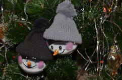 Christmas toys hanging on the tree. Two snowmen in knitted hats stock photography