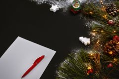 Christmas toys and notebook lying near green spruce branch on black background top view. Space for text Royalty Free Stock Photography