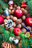 Christmas toys, nuts, fir cones, apples and twigs on a wooden background. Top view Stock Photo