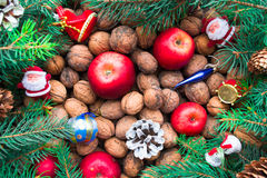 Christmas toys, nuts, fir cones, apples and twigs on a wooden background. Top view Royalty Free Stock Photography