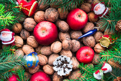 Christmas toys, nuts, fir cones, apples and twigs on a wooden background. Top view Royalty Free Stock Images