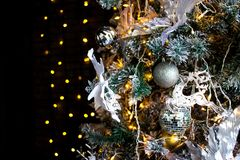 Christmas toys on the pine tree. White deer, orange light bulbs and balls. Dark background. royalty free stock photos