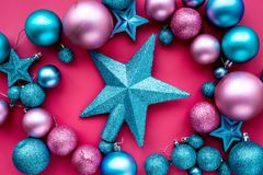 Christmas toys composition. Pink and blue balls and stars on pink background top view Stock Images