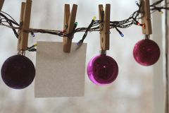 Christmas toys in the shape of balls of crimson and purple shades weigh on clothespins on a snowy blurred background. stock photo