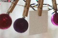 Christmas toys in the shape of balls of crimson and purple shades weigh on clothespins on a snowy blurred background. royalty free stock image