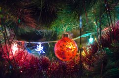 Christmas toys on christmas tree with luminous festoon closeup. New Year`s holiday background. royalty free stock photography