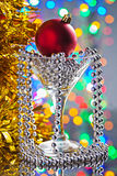 Christmas toys in wineglass on mirror surface Stock Images