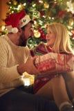Christmas tradition - Cheerful couple with gift enjoying on Chri royalty free stock photography