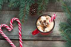 Christmas tradition drink. Mug hot coffee with marshmallow, red candy cane on the wooden background. New Year. Holiday card. Rusti Royalty Free Stock Photos