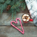 Christmas tradition drink. Mug hot coffee with marshmallow, red candy cane on the wooden background. New Year. Holiday card. Rusti Stock Image
