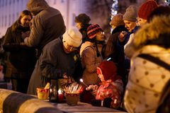 Christmas tradition: people light candles in the evening of Advent. TARTU, ESTONIA - DECEMBER 11, 2016: Christmas tradition: people light candles from the Stock Photos