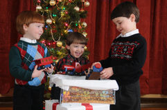 Christmas Train. Three little boys receive a handmade wooden train as a Christmas present royalty free stock photo