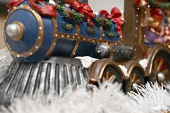 Christmas Train. Front view of a whimsical Christmas train driven by a bear conductor.  Train decorated with Christmas bows and sits on white garland Royalty Free Stock Photography