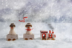 Christmas Train. Set carrying snowmen, one with flying knitted scarf Royalty Free Stock Photography