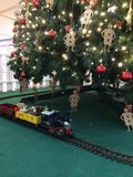 The Christmas train. A toy train on a railroad track with a Christmas tree decorated with the red queen's soldiers Stock Photo