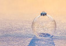 Christmas transparent glass ball with snowflakes on sunset snow. Christmas decoration transparent glass ball with snowflakes shiny in sunset sunlight on snow Royalty Free Stock Photos