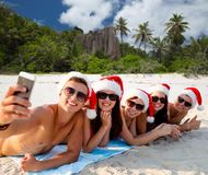 Group of friends in santa hats with taking selfie. Christmas, travel, winter holidays and people concept - group of friends in santa hats taking selfie by stock photo