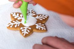 Christmas Treats. The child decorates homemade gingerbread in the form of a snowflake with white and green glaze. Baking holiday c stock images