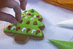 Child hands decorating gingerbread with icing sugar using a pipping bag. Christmas Treats. Handmade cookies, standing on the table royalty free stock photo
