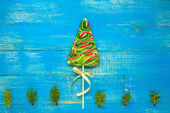 Christmas treats: colorful lollipops in the form of spruce on a blue wooden board. Royalty Free Stock Photo