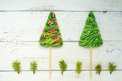 Christmas treats: colorful lollipops in the form of spruce on a white wooden board. Stock Photos