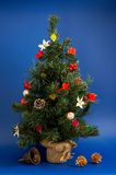 Christmas tree. On a blue background with garlands and handbell Stock Image