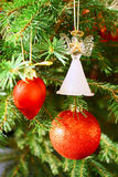 Christmas tree. Red sphere, red heart and glass angel on a Christmas tree royalty free stock image