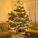 Christmas tree. Beautiful Christmas tree placed in the middle of the corner sofa. Can't get any closer than this Royalty Free Stock Images