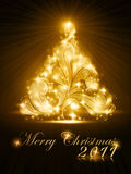 Christmas tree 2011 card with golden glow. Warmly sparkling Christmas tree on dark brown background. Light effects give it a radiating glow. A perfect element in Stock Photography