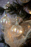 Christmas Tree. Iridescent ornaments, silver beads and glittery silver netting adorn a lighted Christmas tree stock photos