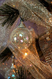 Christmas Tree. Iridescent ornaments, silver beads and glittery silver netting adorn a lighted Christmas tree stock images