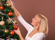 Christmas Tree. Happy young woman decorating Christmas Tree Stock Images