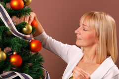 Christmas Tree. Happy young woman decorating Christmas Tree Royalty Free Stock Photos
