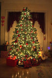 Christmas Tree. In warm home, lights on,presents under tree royalty free stock photography
