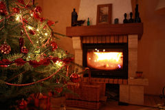 Christmas tree. A Christmas tree next to a fireplace Stock Photo
