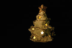 Christmas tree. Dim and warm shot of a hollow christmas tree, lit up from inside, on a black background. Great for white or yellow text Stock Photos