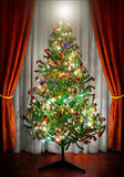 Christmas Tree. Photo of a Christmas tree in a room next to window curtains stock images