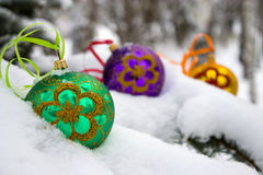 Christmas-tree. Three color christmas baubles sitting in a bed of snow Stock Photos
