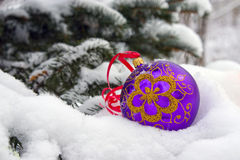 Christmas-tree. A violet christmas bauble sitting in a bed of snow Royalty Free Stock Photography