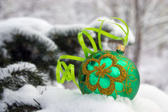 Christmas-tree. A green christmas bauble sitting in a bed of snow Stock Images