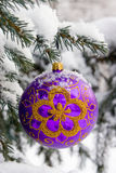 Christmas-tree. Violet christmas glass ball hanging on the tree in snow Stock Photos