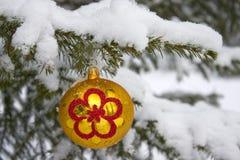Christmas-tree. Yellow christmas glass ball hanging on the tree in snow Stock Photos