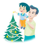 Christmas tree. A father lift up his son to set a star on the tip of christmas tree Royalty Free Stock Photos