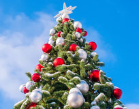 Christmas tree against the sky. Christmas tree decorated with red and white balloons on a background of blue sky Stock Photo